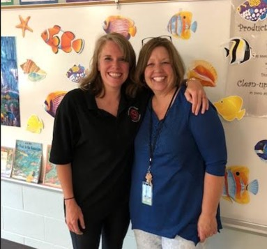 Two teachers standing together and smiling in class.