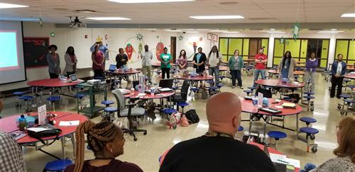 "Teachers at PLA@103 standing in a ""community circle"" discussing pans for the new year."
