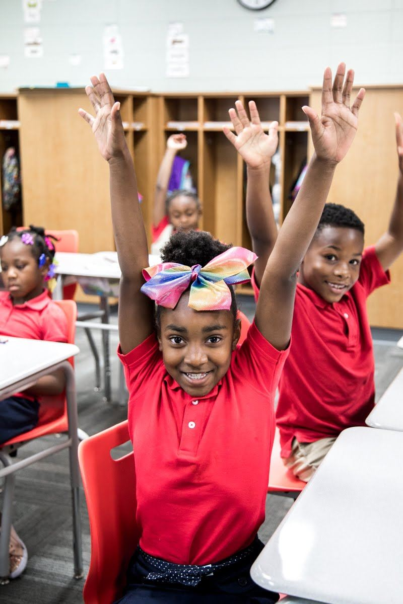 PLA@103 scholars with hands up in classroom
