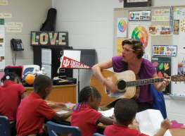 Teacher playing guitar for PLA@103 scholars in the classroom