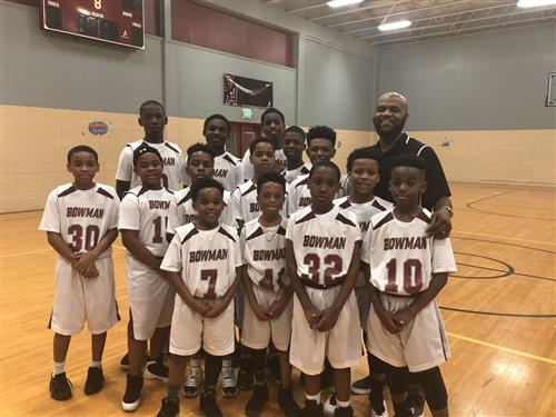 Thea Bowman elementary school basketball team posing in school gym.