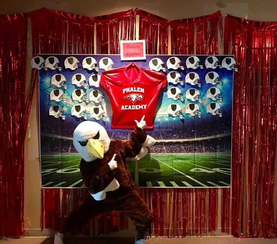 Phalen Falcon Mascot standing in front of bulletin football board.