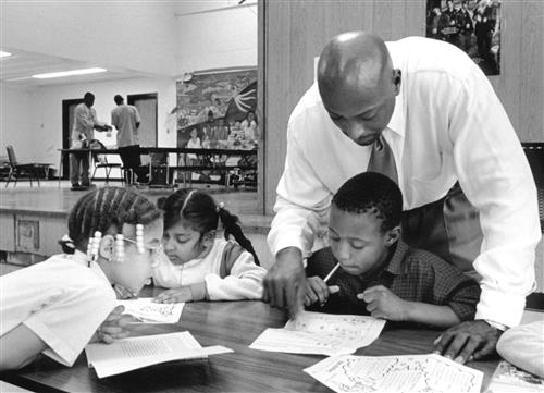 A young Earl Martin Phalen tutoring three students