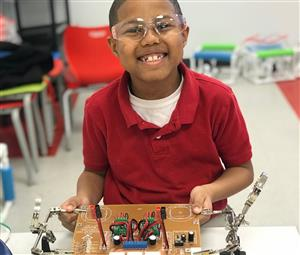 PLA STEM student smiling in front of engineering board
