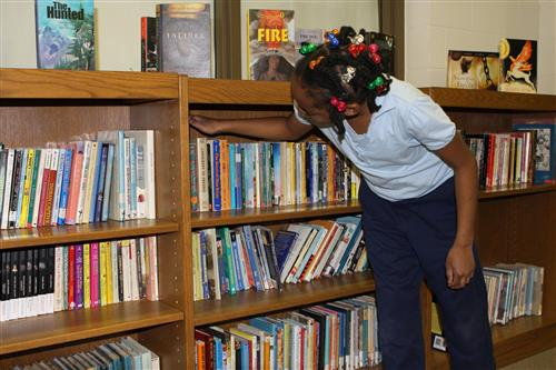 Student looking through books at the TLJ library.