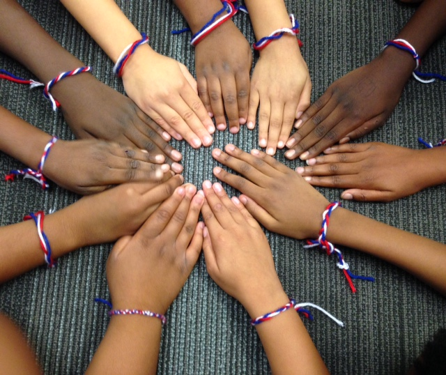 Children wearing red, white, and blue bracelets with their hands in a circle