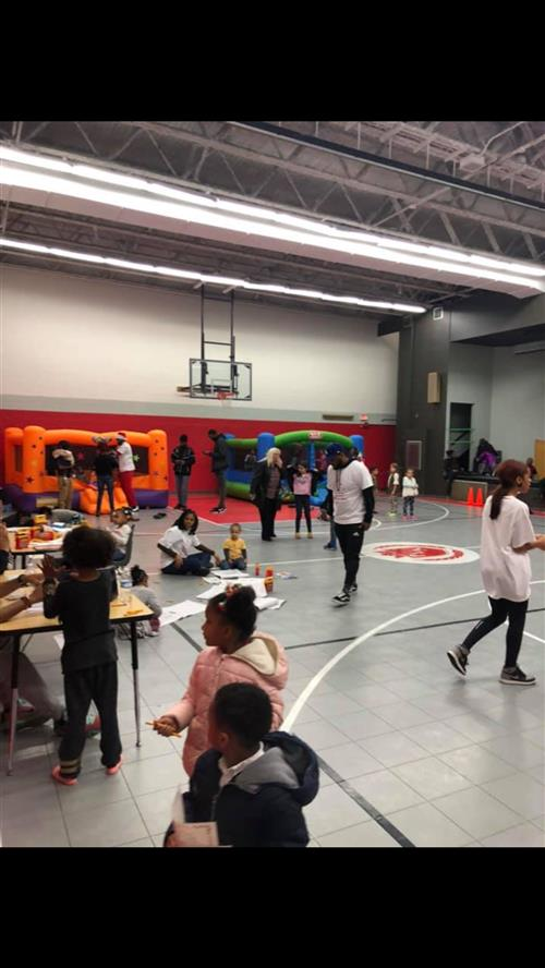 The gymnasium filled with kids playing on bounce houses and doing holiday activities.